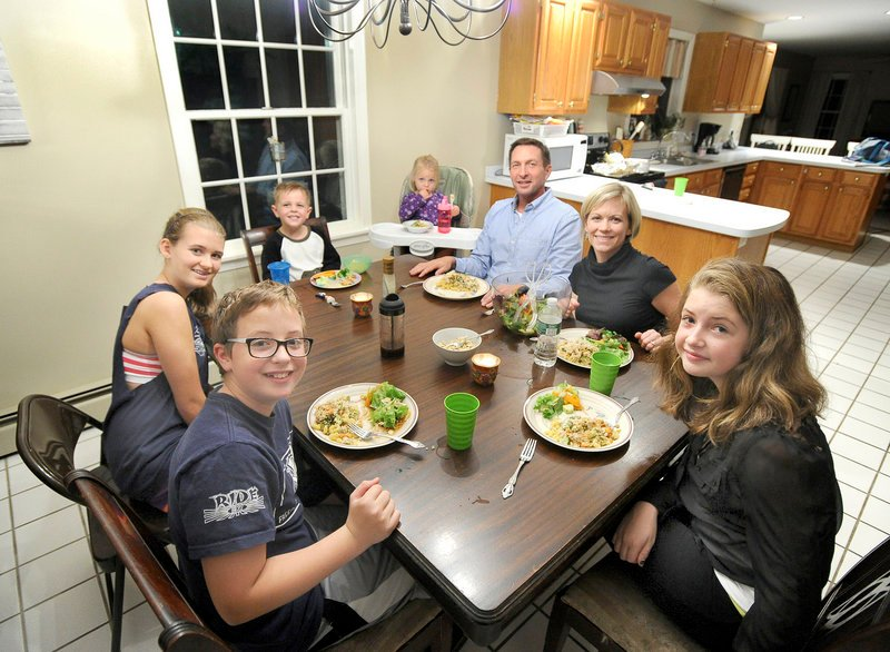 """The Peterson family sits down for a dinner of creamy vegan """"chicken"""" casserole with chopped-pumpkin-seed tossed salad recently at their Portland home. Clockwise from lower left, Bryant Peterson, 13, Madison Legassey 13, Brady Peterson, 4, Gabriela Peterson, 2, Jeff Peterson, Laura Peterson and Carly Peterson, 12."""