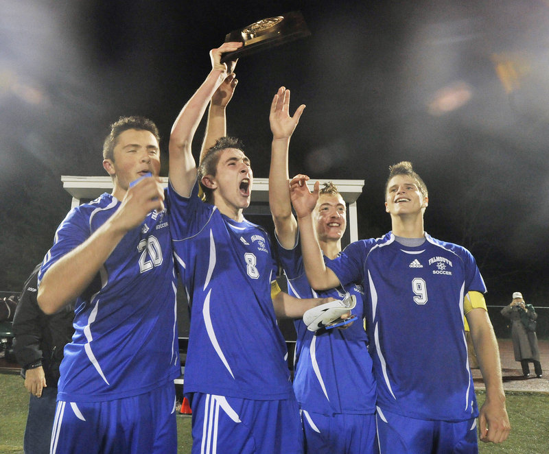 Falmouth's Jack Pike, left, Cooper Lycan, Grant Burfeind and JP White raise their trophy after topping Yarmouth 2-0 for the Western Class B soccer championship Wednesday.