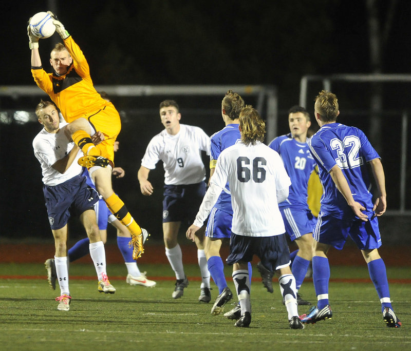 Falmouth goalie Will D'Agostino pulls down a high shot in heavy traffic in front of his goal against Yarmouth.
