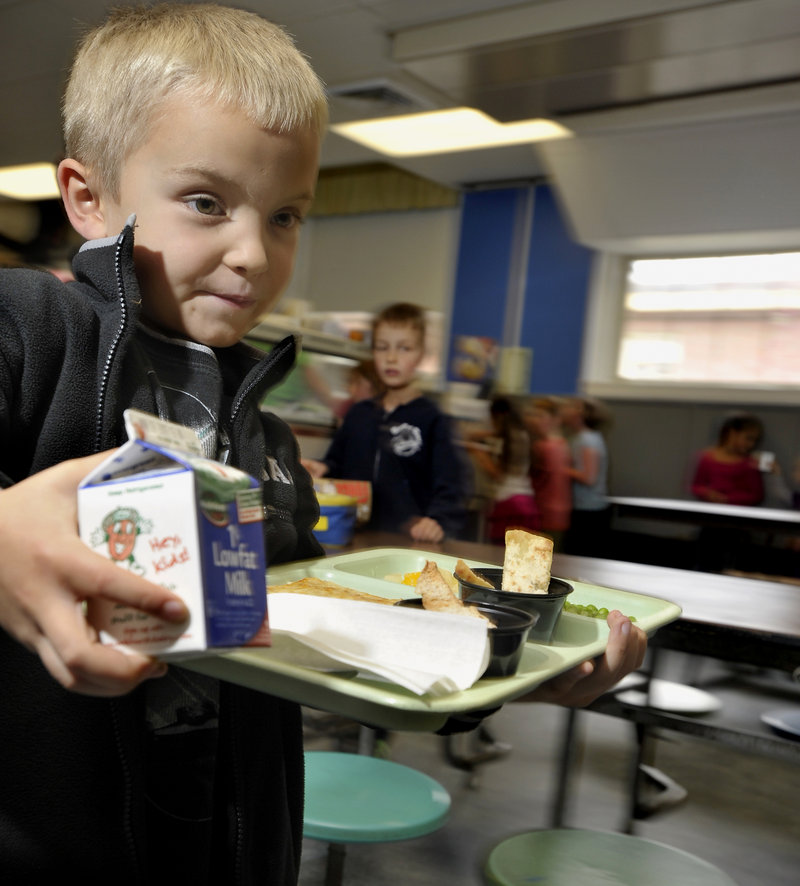 Tyler Hussey, 6, heads to his seat with pita chips, carrot slaw and hummus to go with his pizza and milk.