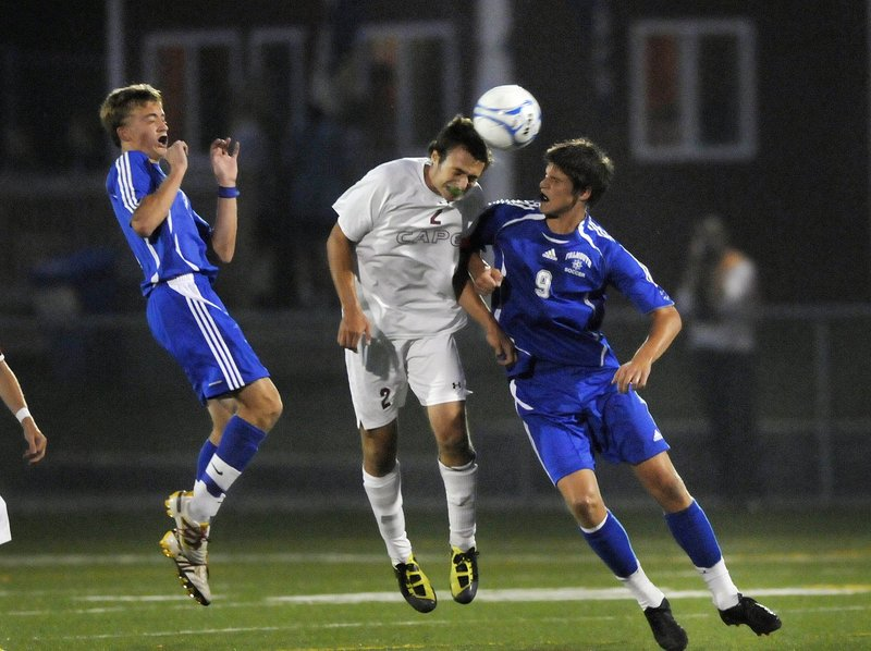 Cape Elizabeth's Brian Brett goes up for a header against Falmouth's J.P. White during soccer action on Sept. 14, 2011.