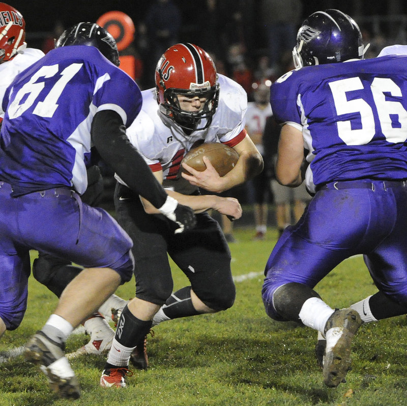 Dante Fanning tries to cut through rugged Marshwood defenders Eric Pratt (61) and Tyler Gagnon (56). Marshwood's defense, so vulnerable earlier in the season against Wells, stiffened considerably in the rematch.