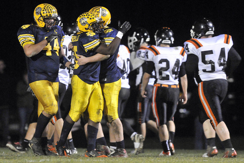 Kindle Bonsall, center, celebrates with quarterback Jordan Whitney, right, after catching a 24-yard touchdown pass in the second quarter of Mt. Blue's 33-21 win over Gardiner.