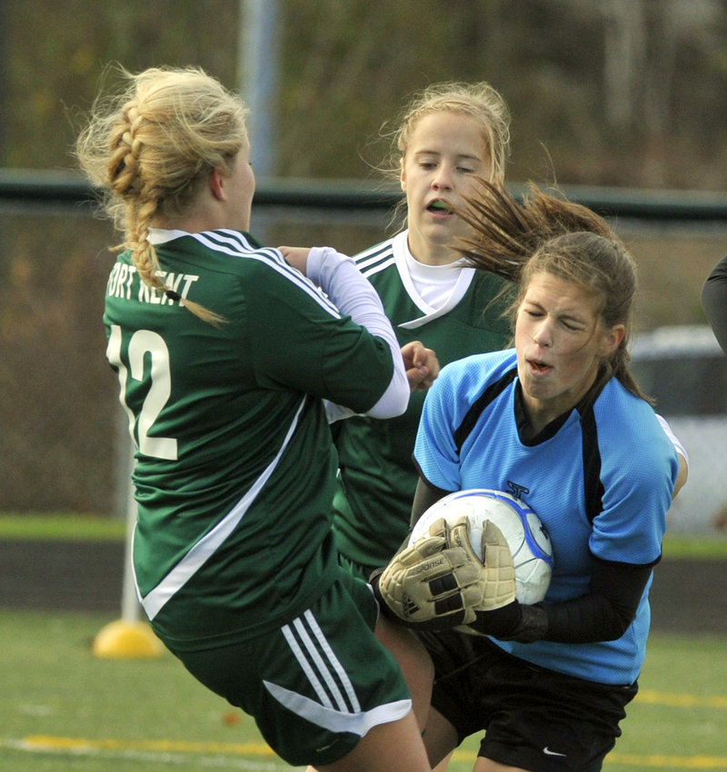 Juliana Harwood of Waynflete grabs a loose ball before Steffany Paradis, left, and Jessica Moring of Fort Kent during the Class C state final at Scarborough.