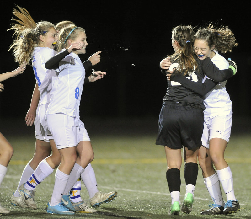 Falmouth goalie Caroline Lucas, black shirt, gets hugs all around from her Falmouth teammates after they secured the Class B title.