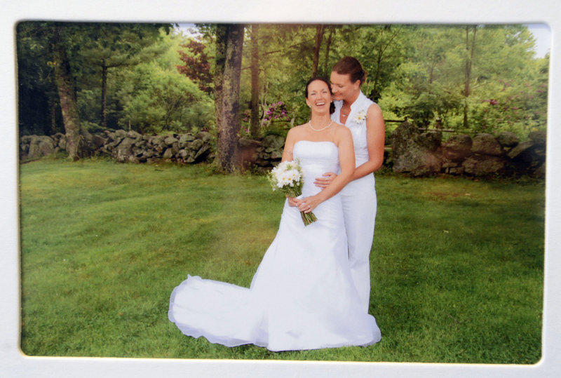 Alissa Poisson and Maggie Oechslie of South Portland in a family photo on display in their home from June of 2011 when they had a commitment ceremony in Cape Neddick.