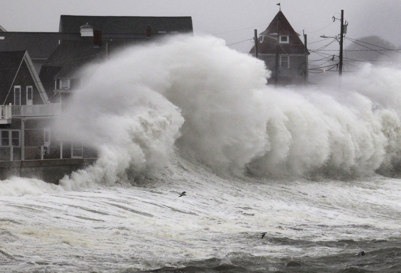 Waves crash into a seawall and buildings along the coast in Hull, Mass., which was feeling the effects of a nor'easter Wednesday, just like New York and New Jersey. A high wind warning was in effect.