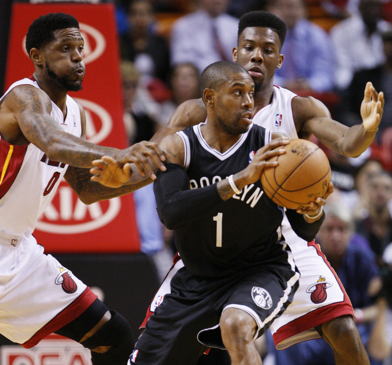 C.J. Watson of the Brooklyn Nets looks for an opening Wednesday night while guarded by Udonis Haslem, left, and Norris Cole of the Miami Heat during Miami's 103-73 victory.