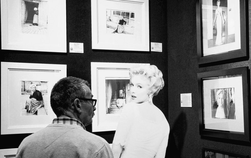 A potential bidder looks at Marilyn Monroe photos prior to an auction of pictures by the late celebrity photographer Milton H. Greene in Warsaw, Poland.