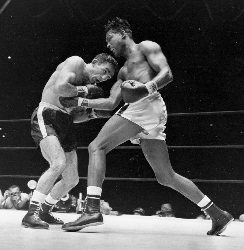 Carmen Basilio, left, bores during his upset of world middleweight champion Sugar Ray Robinson at Yankee Stadium on Sept. 23, 1957.