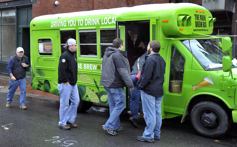 Zach Poole, right, greets tour members as they board the Maine Brew Bus behind the Thirsty Pig for a tour of two beer breweries, a meadery, a coffee roaster, a fermenter and distiller over several hours Thursday.