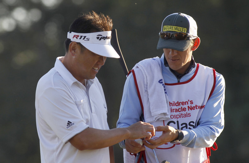 Charlie Wi, left, hands a ball to caddy Mark Urbanek, after finishing his first round at the Children's Miracle Network Hospitals Classic at Lake Buena Vista, Fla., on Thursday.
