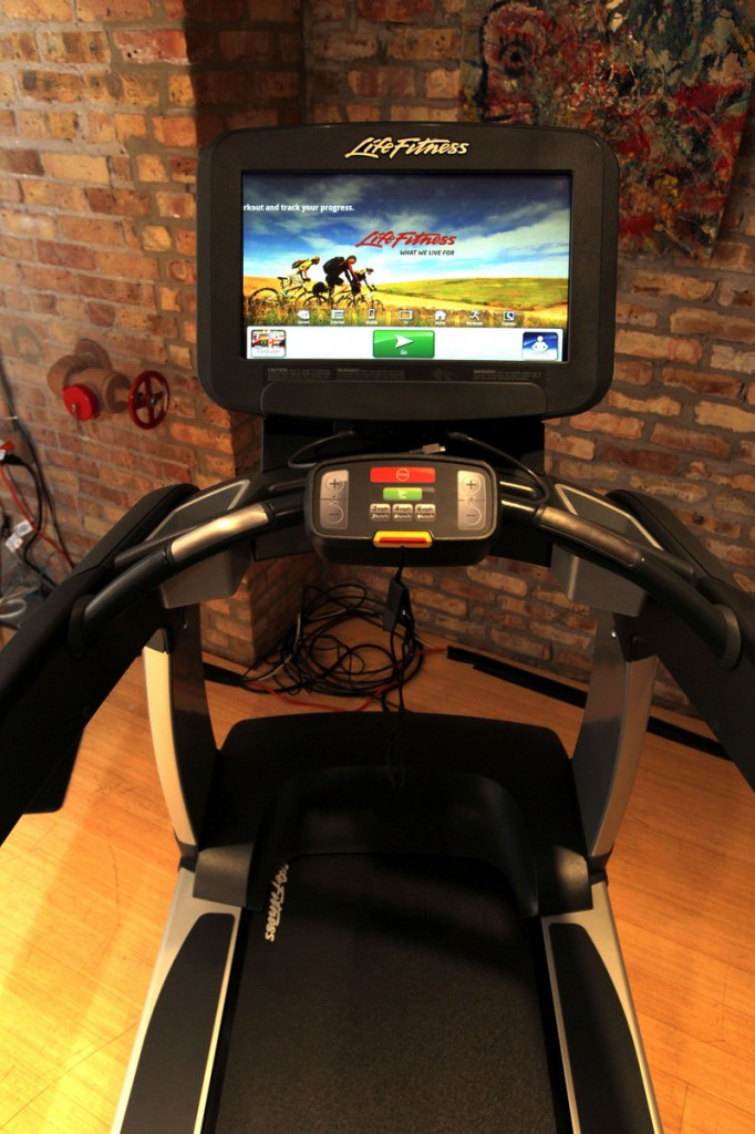 A new Life Fitness treadmill with a large monitor is on display at a company event in Chicago.
