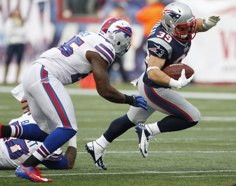 Danny Woodhead swerves around Buffalo safety Da'Norris Searcy during first-half action of Sunday's game in Foxborough, won by the Patriots 37-31.