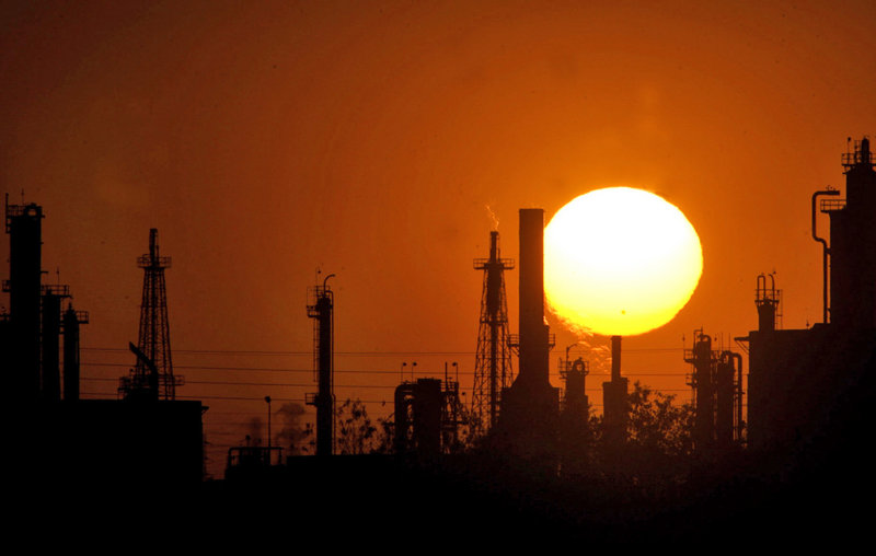 The sun sets behind an oil refinery in Bakersfield, Calif. On Wednesday, the state is launching a cap-and-trade system meant to control emissions of heat-trapping gases, hoping the program provides a blueprint for other governments, says the California Air Resources Board.