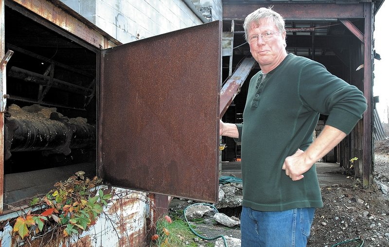 """Jay Strickland of Bingham, who recently purchased the former Kennebec Mill, checks out the inside of an old silo on the property recently. """"The building is here, and if we don't do anything with it, it's just going to fall down. I'm trying to bring Bingham back,"""" he said."""