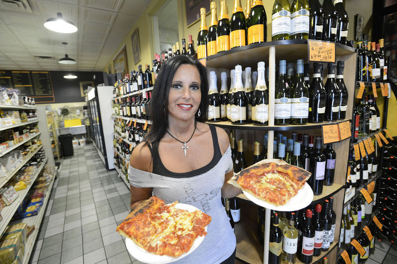 Anna Micucci hoists two servings of Stephen Lanzalotta's Sicilian slab pizza at Micucci's in Portland.