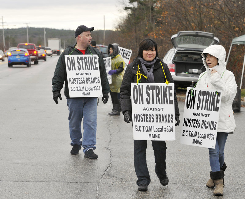 Union employees picket Tuesday outside the Hostess Brands plant in Biddeford to protest cuts in wages and benefits. The workers went on strike Friday evening after the last loaf of bread was wrapped.