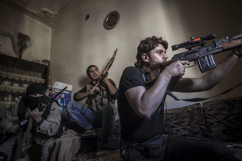 A rebel sniper aims at army positions in Syria. The rebels are seeking more powerful weapons from other countries.