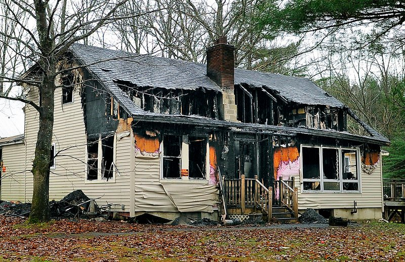 This house at 580 Dow Road in Orrington, scene of a multiple-fatal fire Saturday, stands charred from the inside out on Tuesday. Fire Chief Michael Spencer says he hopes the tragedy can renew a focus on safety.