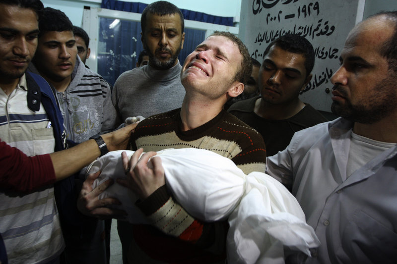Jihad Masharawi weeps over the body of his 11-month-old son Ahmad after an Israeli air strike hit their home in Gaza City Wednesday. Israel's attack killed at least 10 Palestinians.