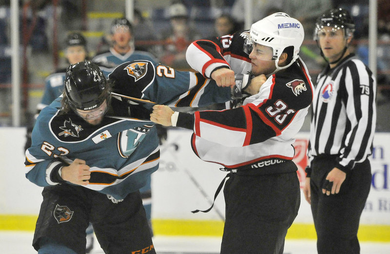 Mark Louis of the Portland Pirates, right, unleashes a punch against Matt Pelech of the Worcester Sharks during the first period of Worcester's 4-2 victory Wednesday night at Lewiston. Each player received a major for fighting.