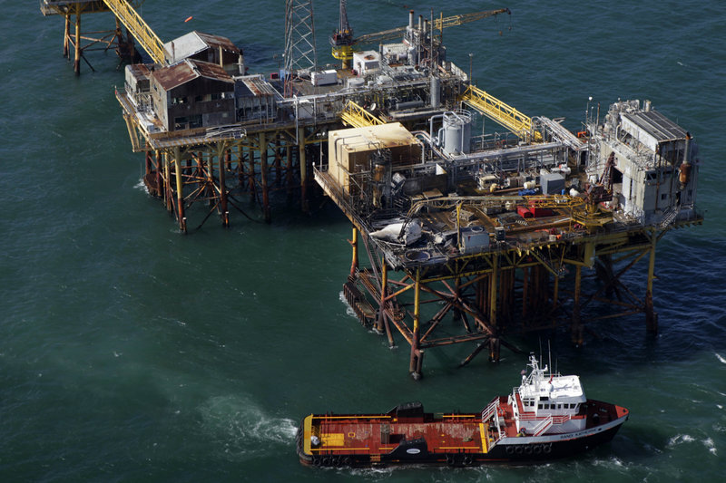 Aerial photograph shows a supply vessel moving near an oil rig damaged by an explosion and fire on Friday. The oil rig is in the Gulf of Mexico, about 25 miles southeast of Grand Isle, La.