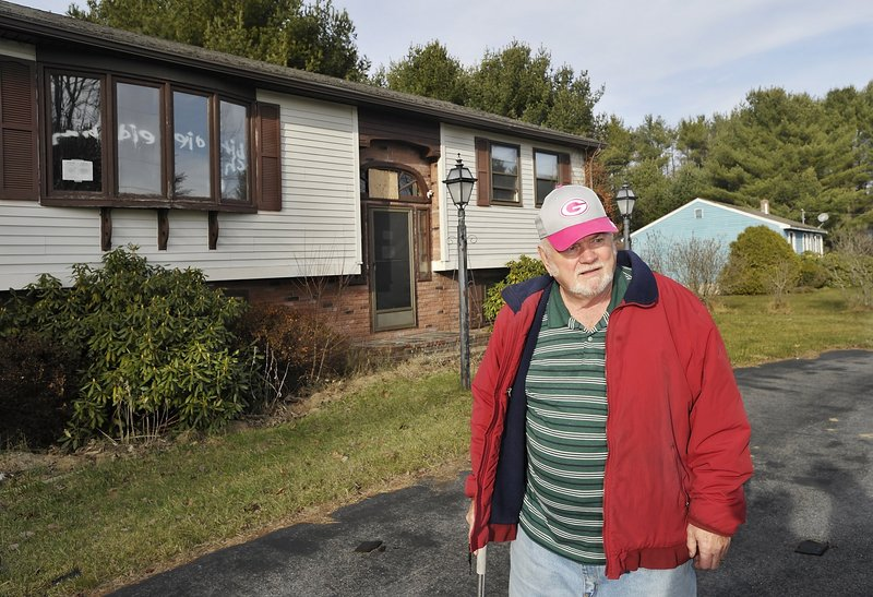 Earl Jamieson, 74, stands in front of a dilapidated house, which he says is bringing down neighborhood property values, on Mary Avenue in Saco. He is trying to sell his own property next door.