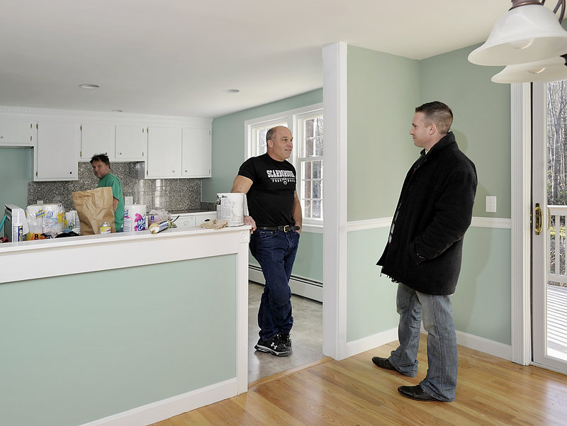Realtor Marty Macisso, right, chats with owner Jeff Quirk, who is fixing up a house that he bought in Scarborough after it was repossessed by a bank in a default. Quirk is buying such properties at auction, fixing them up and reselling them.