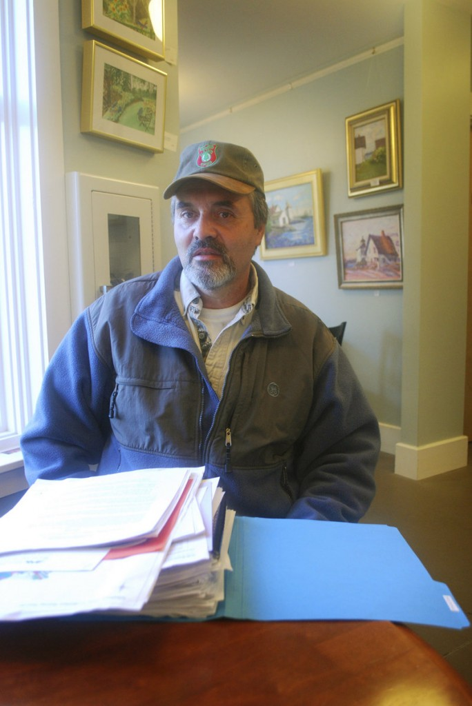 """Fred Thomas sits behind a year's worth of research that he collected as chairman of the Islesboro Deer Reduction Committee. """"It's been quite a task,"""" Thomas said."""