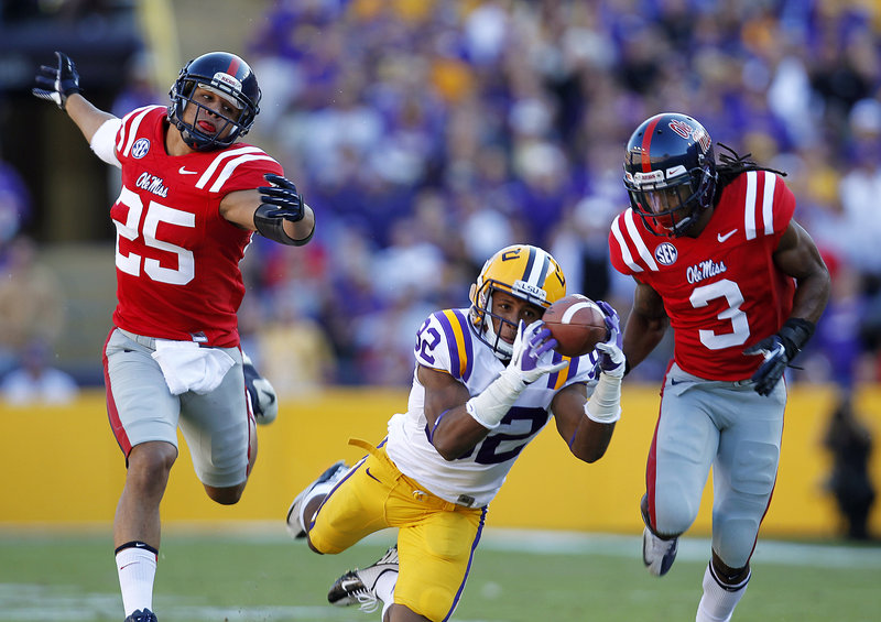 LSU wide receiver James Wright pulls in a 48-yard pass reception while sandwiched by Mississippi defensive backs Cody Prewitt (25) and Charles Sawyer (3) during the Tigers' 41-35 victory in Baton Rouge, La., Saturday.