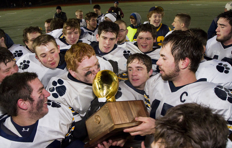 Jordan Whitney, the Mt. Blue quarterback, right, holds the Gold Ball for a teammate to kiss Saturday night after the Cougars beat Marshwood to win the Class B title.