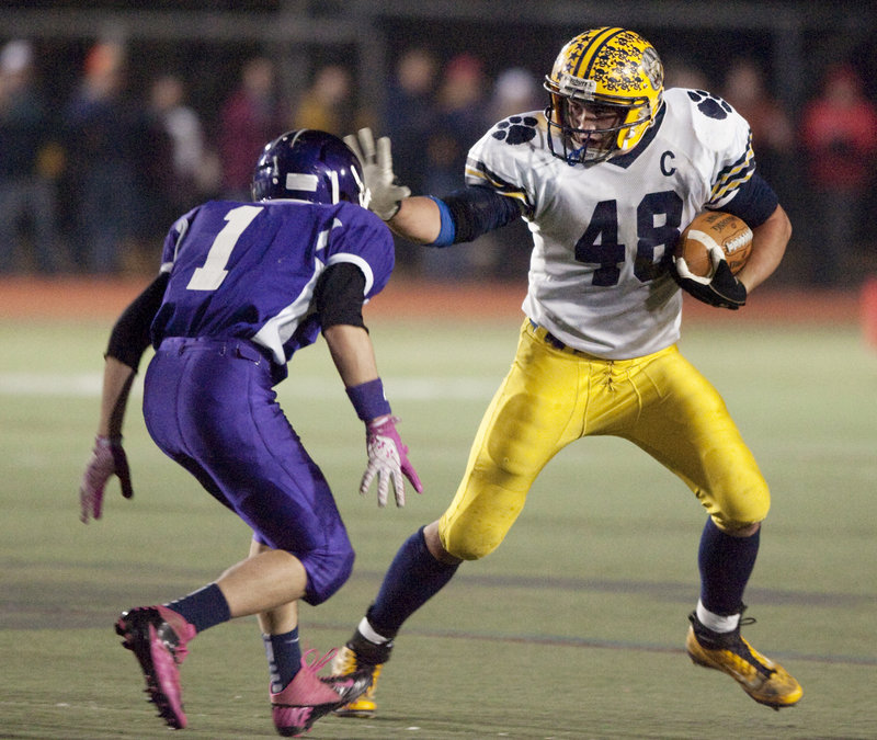 Chad Luker of Mt. Blue attempts to fend off Lucas Blanchette of Marshwood during the Class B state final Saturday night. Luker scored five touchdowns on short runs in a 44-42 victory at Fitzpatrick Stadium.