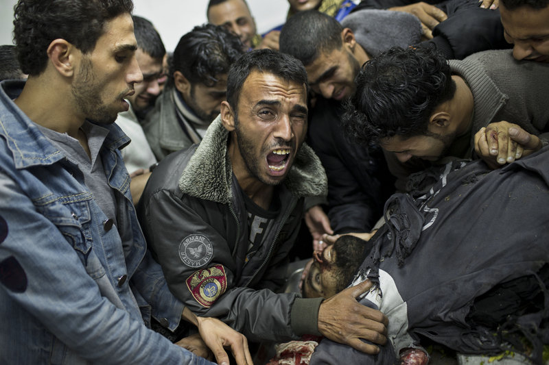 A Palestinian man cries over the body of a dead relative in the morgue of Shifa Hospital in Gaza City on Sunday. The Israeli military carried out dozens of airstrikes throughout the day, while Palestinian militants continued to barrage Israel with more than 100 rockets.