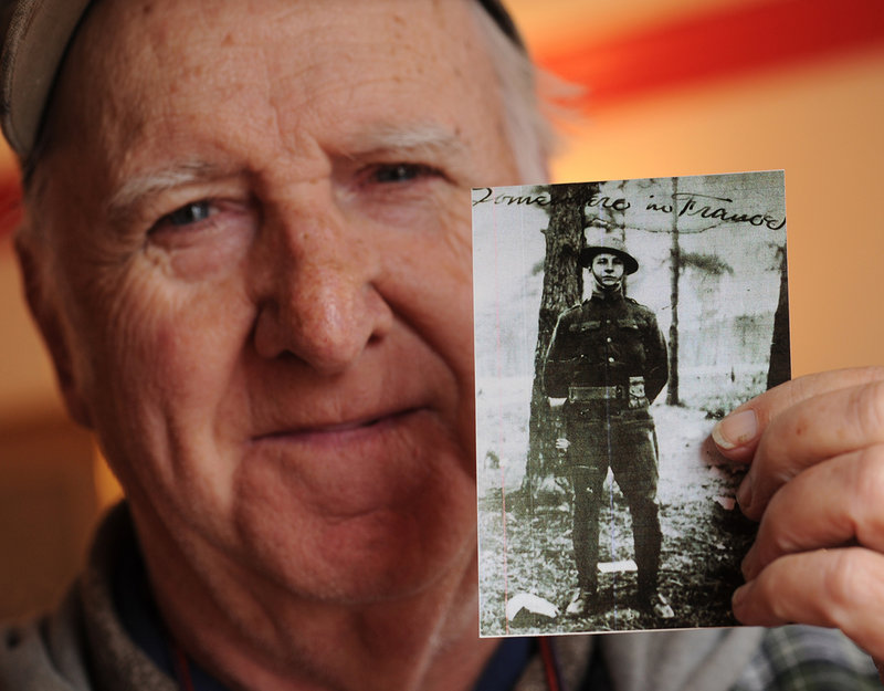n this Friday, Nov. 2, 2012 photo John Mayo, 76, displays a World War I era photo of his father U.S. Army Pfc. Frederick Mayo, at the Lafayette-Durfee House, in Fall River, Mass. Drawings by Mayo, who for 26 months was one of the