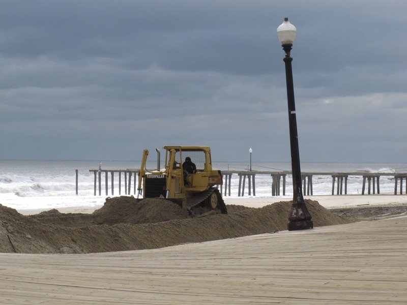 A bulldozer pushes piles of sand on the Ocean Grove, N.J., beach in front of its storm-buckled boardwalk and damaged fishing pier last week.