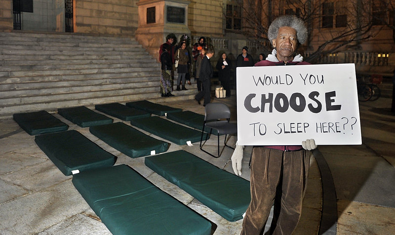 Nick Nicholson with Homeless Voices for Justice stands near pads that homeless people sleep on at shelters, as he and other advocates hold a vigil Monday evening outside Portland City Hall.