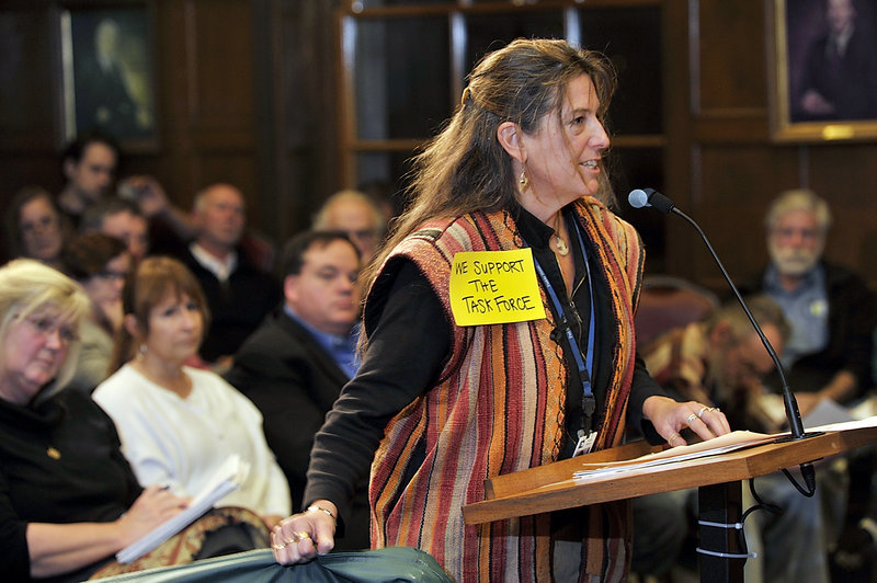 Donna Yellen of Preble Street holds a shelter mattress as she speaks to the council and challenges the notion that homeless people come to Portland for the services provided.