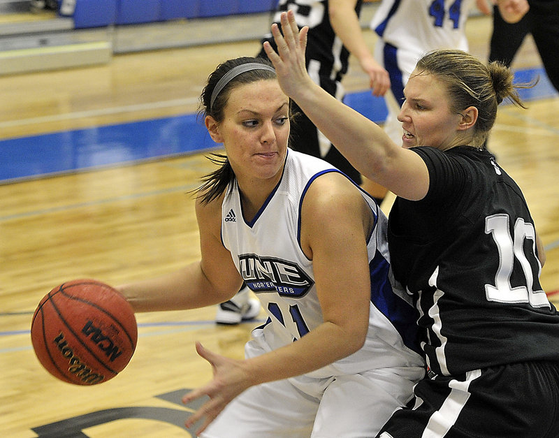 Liz LeBlanc of the University of New England looks for room to drive Tuesday night while pressured by Kirsten Prue of Bowdoin. UNE opened a new building by winning, 72-32.