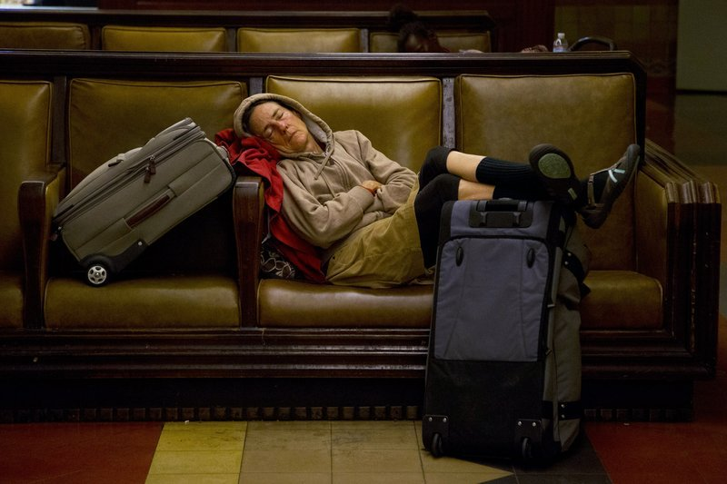 A traveler sleeps Wednesday at Union Station in Los Angeles. About 43.6 million Americans were expected to journey 50 miles or more between Wednesday and Sunday, a slight increase over last year, and evidence that Americans are continuing to recover from the recession of 2007-09.