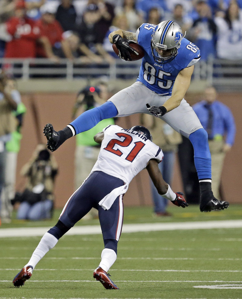 Tony Scheffler of the Detroit Lions leaps over Houston defensive back Brice McCain during overtime Thursday. The Texans improved to 10-1 with a 34-31 victory.
