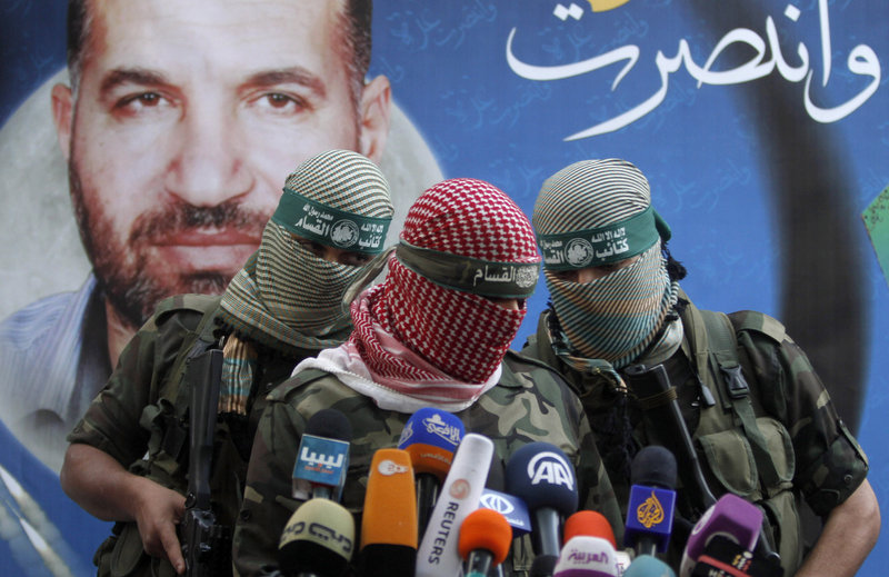 "Hamas militants talk during a press conference in Gaza City on Thursday. The poster reads: ""Gaza won"" and shows Ahmed Jabari, the Hamas leader assassinated on Nov. 14, which set off the last round of fighting."