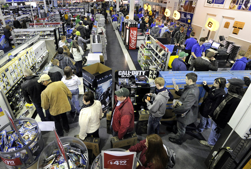 Best Buy's general manager Bart Gillespie, center, fires up his team before the South Portland store opened at midnight Thursday. The team tried to pace the number of shoppers allowed in at one time.