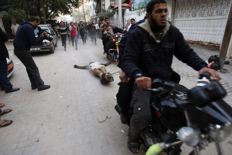 """Palestinian gunmen drag the body of a man who was killed for allegedly collaborating with Israel through Gaza City on Tuesday. The military wing of the Palestinian militant group Hamas claimed responsibility for the deaths of the man and five other suspected collaborators. The killings are """"a recent demonstration of the Hamas approach to Gazans suspected of supporting Israel,"""" says an Israeli-American reader."""