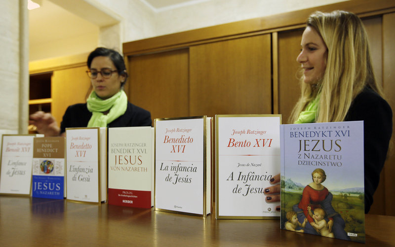 Editions of the book in different languages are displayed on a desk during its official presentation.