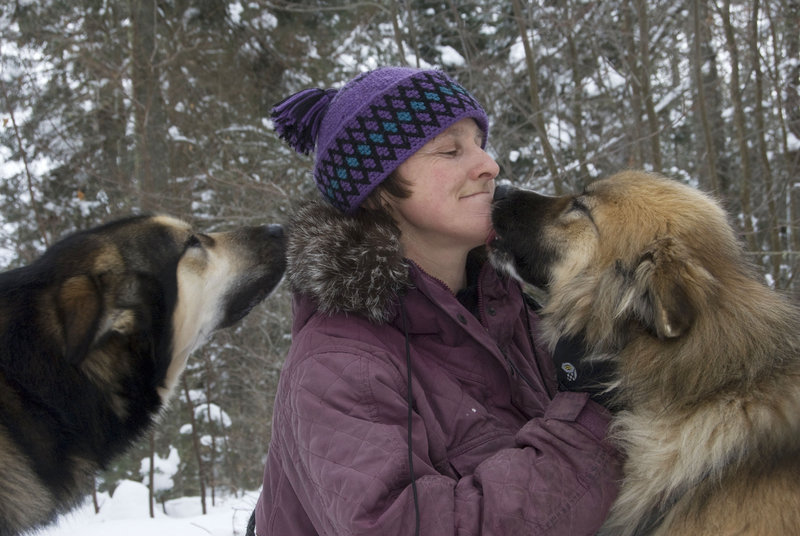 Dogsledder Polly Mahoney gets mushy with a couple of her sled dogs, above, and goes out on a run with her team of huskies, below. Mahoney, of Mahoosuc Guide Service in Newry, will share slides of her dogsledding experiences in a 7 p.m. talk Thursday at the Camden Public Library. She will bring a few of her dogs, too. For more details, call Ken Gross at 236-3440.