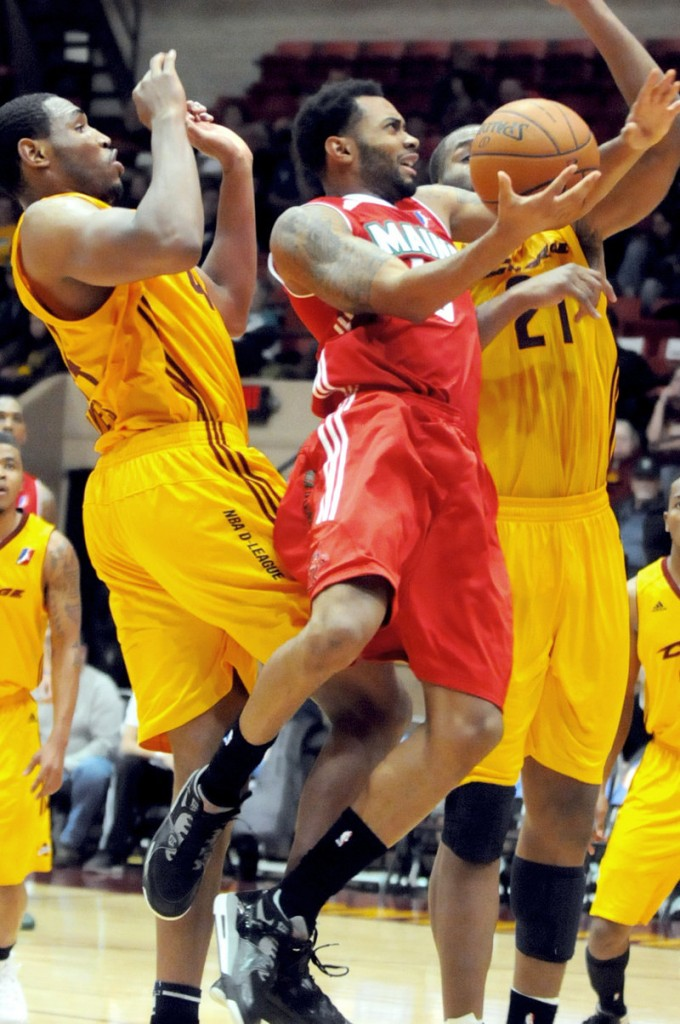 Xavier Silas of the Maine Red Claws drives to the basket between Kevin Jones, left, and Arinze Onuaku of the Canton Charge during the Red Claws' 123-115 victory in an opener Friday night.