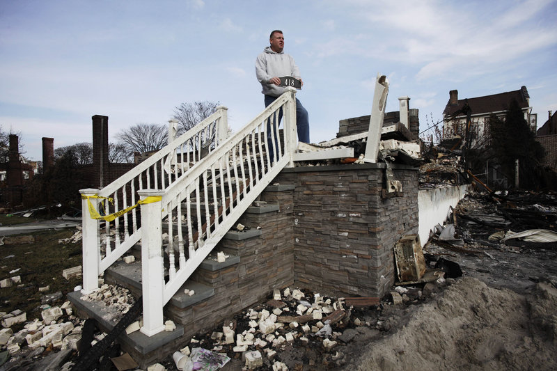 Ray Marten poses by his destroyed home in Queens, N.Y., which burned when Sandy hit the area. Rebuilding is expected to provide the region a huge economic boost.