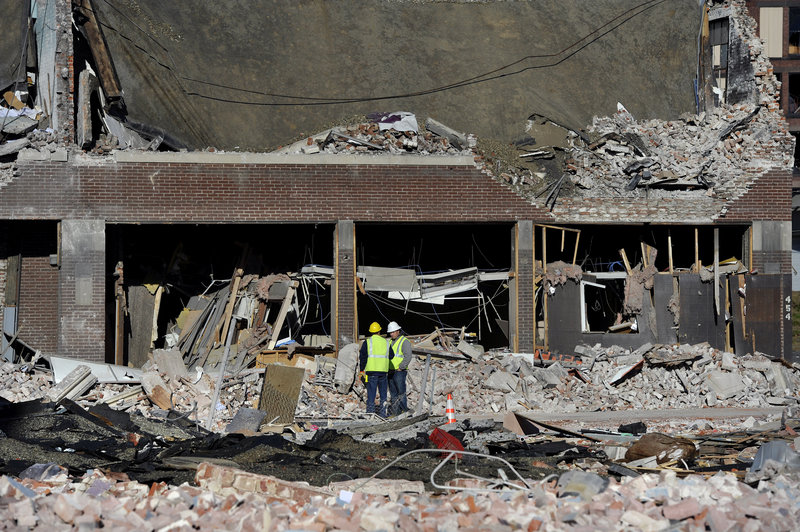 Inspectors stand in debris Saturday at the site of a gas explosion that damaged dozens of buildings and injured 18 people in Springfield, Mass., on Friday evening.