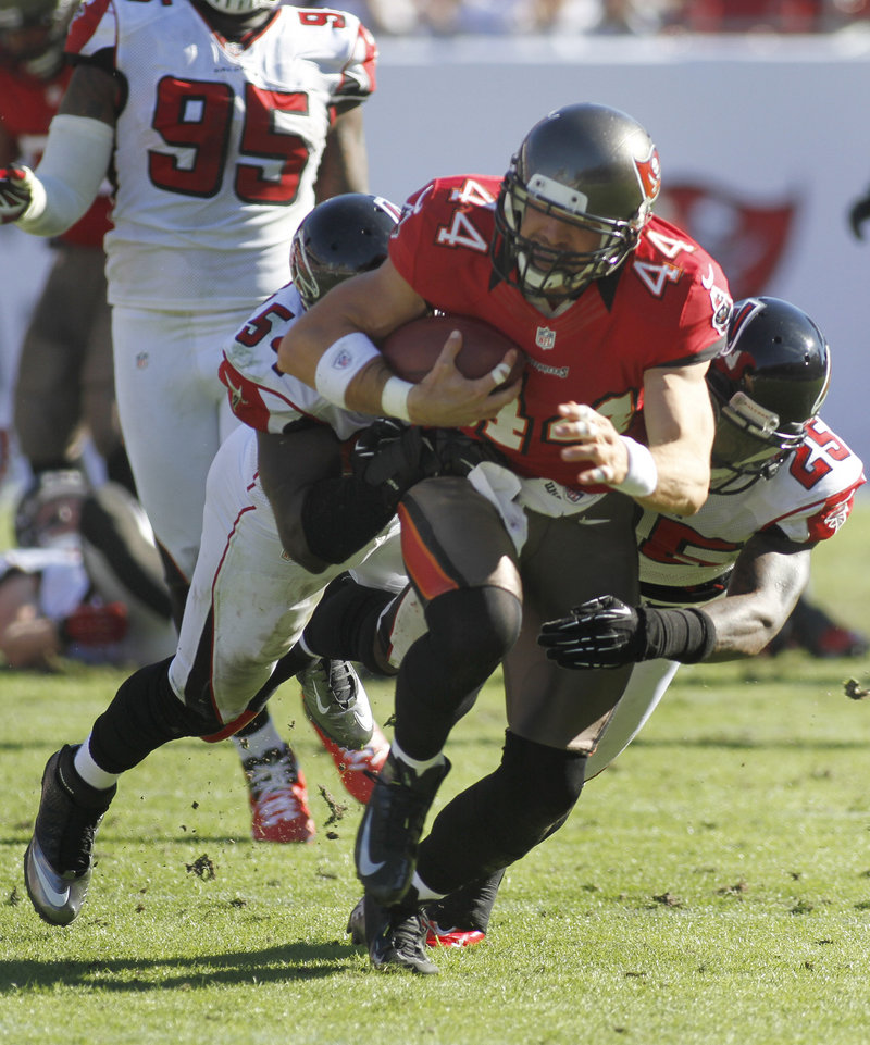 Dallas Clark, tight end for Tampa Bay, drags Atlanta defenders Stephen Nicholas (54) and William Moore (25) following a reception in Sunday's loss to the Falcons.